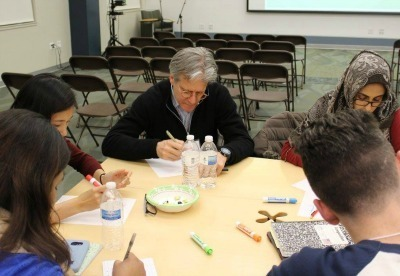 IDEO co-founder, Dennis Boyle, sits with students as they generate ideas